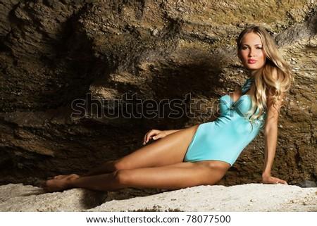 Beautiful fashionable woman in blue bikini in the rock - stock photo