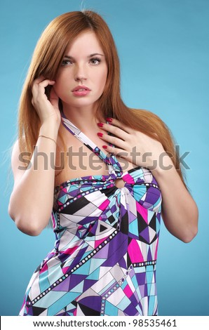 Beautiful fashionable woman in colorful sundress against blue background - stock photo