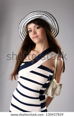 Beautiful fashionable woman in stripped hat and dress - stock photo