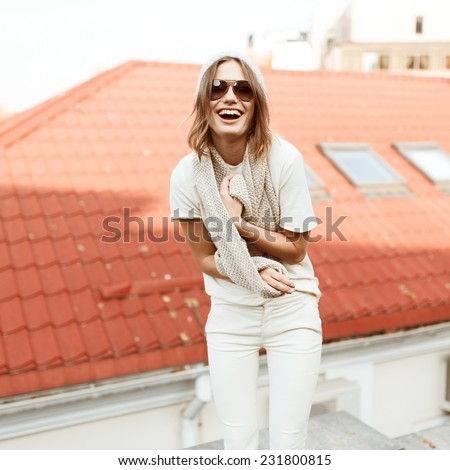 Beautiful fashionable woman laughing in the street against the background of roofs