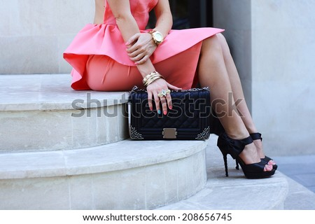 beautiful fashionable woman legs in shoes high heels and handbag at the street - stock photo