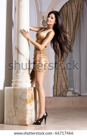 beautiful fashionable woman near the column - stock photo
