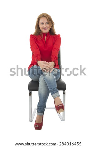 Beautiful fashionable woman sitting on a chair against a white background - stock photo
