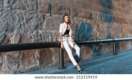 Beautiful fashionable woman standing in white shirt and pants near the wall - stock photo