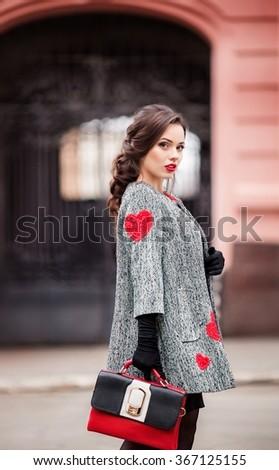 Beautiful fashionable woman standing on the city street.  - stock photo