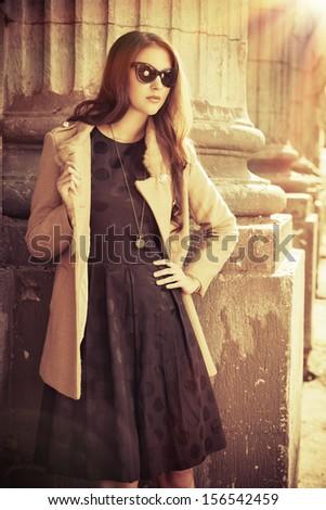Beautiful fashionable woman standing on the city street. Sepia. - stock photo
