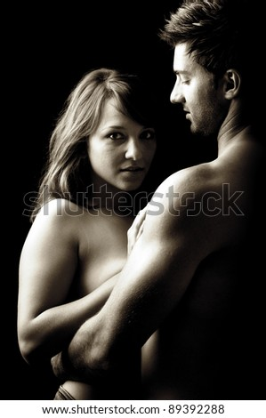 Beautiful fashionable young couple isolated in black