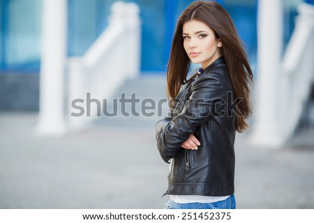 Beautiful fashionable young woman outdoor. glamorous portrait of young beautiful woman in a leather jacket. beautiful girl portrait. Beautiful fashionable woman standing on city street. Fashion Look - stock photo