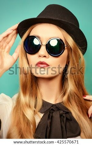 Beautiful fashionable young woman wearing elegant blouse, hat and sunglasses. Studio shot over aquamarine background. - stock photo