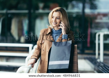 Beautiful, fashionable, young woman with shopping bags talking on cell phone and smiling. Outdoor city street portrait.
