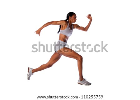Beautiful fast running female athlete with toned muscular fitness body in grey with headset listening to music while exercising, isolated. - stock photo