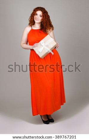 beautiful fat girl with red hair with a gift box in hand on gray background