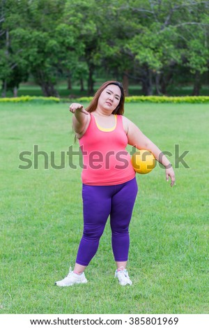 Beautiful fat woman playing yellow ball in the park. in the park. - stock photo