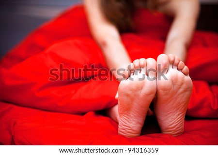 Beautiful feet of a young woman lying in bed, closeup - stock photo