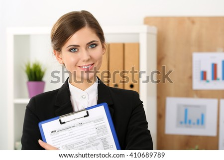 Beautiful female accountant hold income tax return form portrait. Internal Revenue Service inspector checking financial document, 1040, planning budget, certified public accountant concept - stock photo