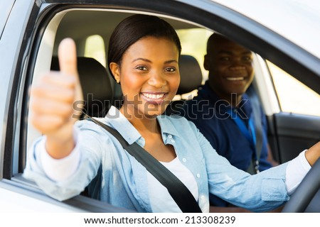 beautiful female african learner driver with instructor giving thumb up - stock photo