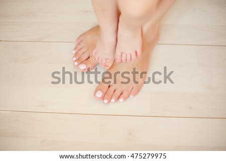 beautiful female and children's feet on a light floor