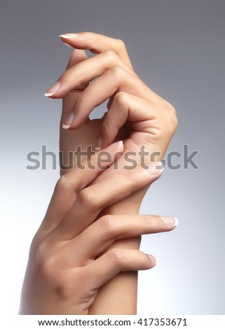 Beautiful female arms with ideal french manicure on grey background. Care about female hands, healthy soft skin. Spa & cosmetics. Beauty care. Close-up of beautiful famele fingers with nails polish - stock photo