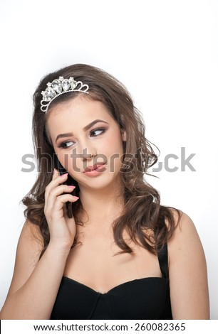 Beautiful female art portrait with beautiful eyes wearing a tiara speaking on mobile. Genuine natural brunette with jewelry, studio shot. Portrait of a attractive woman with tiara and creative make up - stock photo