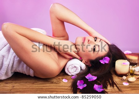 Beautiful female at spa salon, lying down on massage bed, sexy woman taking care of her body, spa treatment and healthy lifestyle concept - stock photo