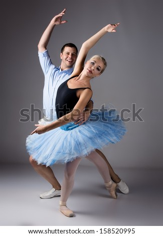 Beautiful female ballet dancer and her instructor on a grey background. Ballerina is wearing a black leotard, pink stockings, pointe shoes and a blue tutu.