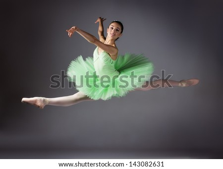 Beautiful female ballet dancer on a grey background. Ballerina is wearing a green tutu and pointe shoes. - stock photo