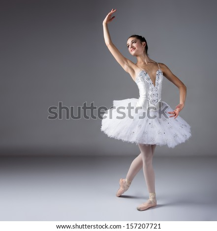 Beautiful female ballet dancer on a grey background. Ballerina is wearing a white tutu and pointe shoes. - stock photo