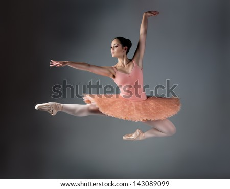 Beautiful female ballet dancer on a grey background. Ballerina is wearing an orange tutu, pink stockings and pointe shoes. - stock photo