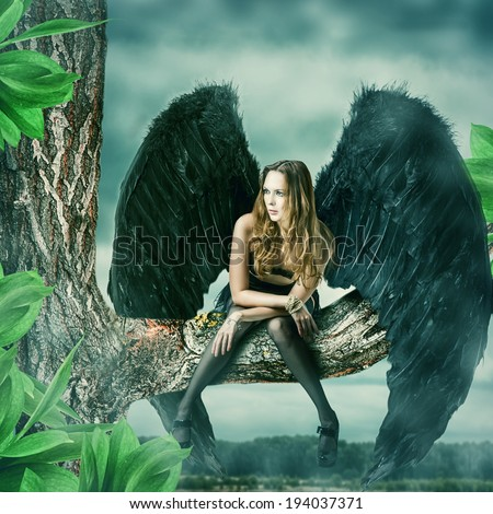 Beautiful female black angel sitting on a tree