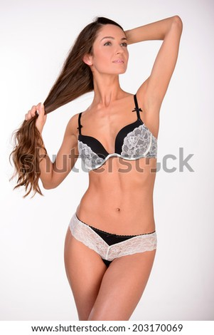 Beautiful female body. Beautiful young woman in lingerie while standing against white background