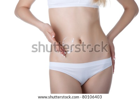 Beautiful female body isolated on white background. Sexy young woman in white panties. applying moisturizer cream on stomach. Perfect female figure. Body beauty concept. - stock photo