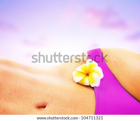 Beautiful female body on the beach, perfect shape slim fit figure, sexy woman over pink sunset sky, girl relaxing in bikini, sunbathing tan skin, conceptual image of vacation, spa and summer holidays - stock photo