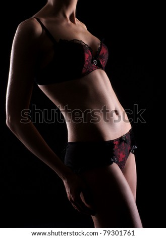 Beautiful female body over black background