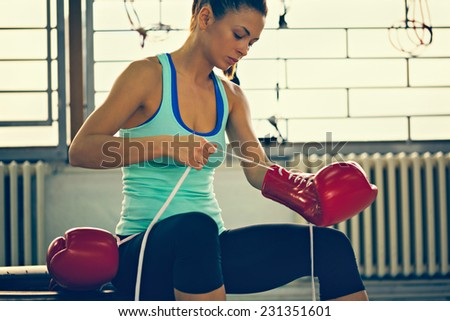 Beautiful Female Boxer Binding Boxing Gloves - stock photo