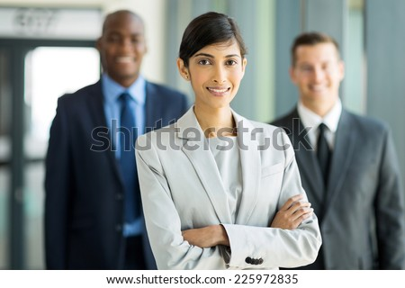 beautiful female business leader with team standing on background