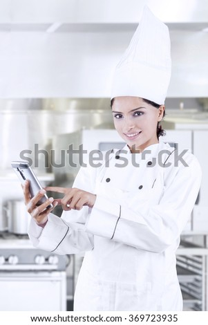 Beautiful female chef searching menu online with smartphone in the restaurant kitchen