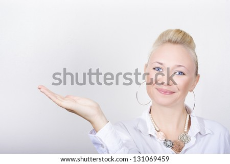 Beautiful Female Cosmetologist Selling Skincare And Cosmetics Range With A Hand Gesture To Copyspace In A Aesthetician Concept - stock photo