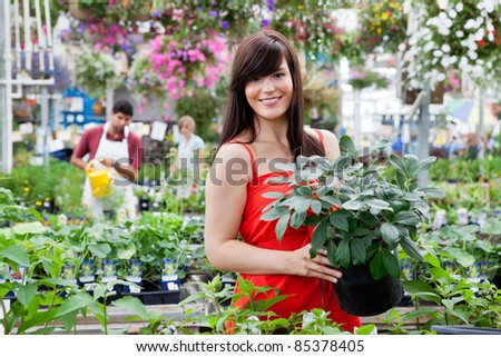 Beautiful female customer holding potted plant with workers in background