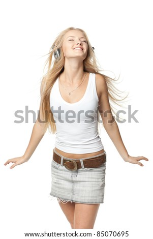 Beautiful female dancing to the music in headphones with fluttering on the wind hair over white background