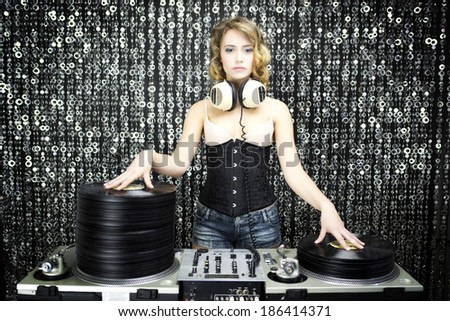 beautiful female dj with pile of vinyl records - stock photo