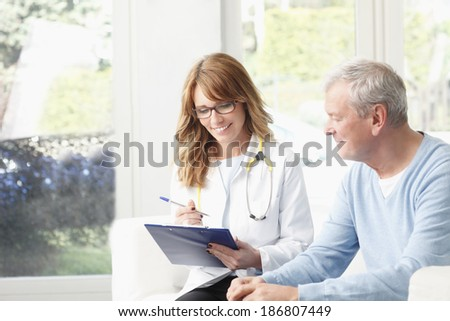 Beautiful female doctor analyzing x-ray with senior patient at small clinic.