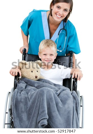 Beautiful female doctor carrying adorable little boy in the wheelchair at the hospital - stock photo