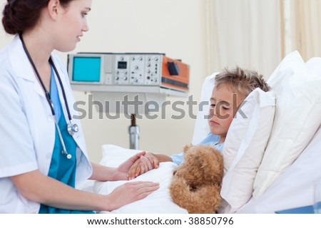 Beautiful female doctor examining a child in bed - stock photo