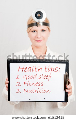 Beautiful female doctor giving health tips - text sleep, fitness, nutrition - stock photo