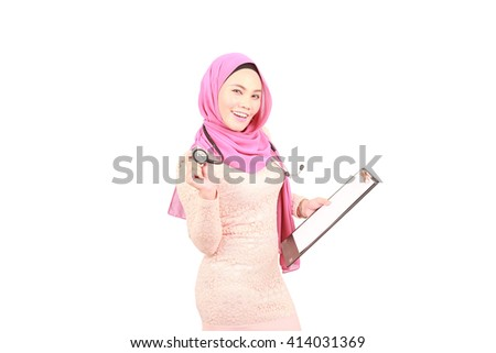 Beautiful female doctor holding a clipboard and stethoscope - stock photo