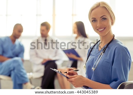 Beautiful female doctor is making notes, looking at camera and smiling, in the background three medical doctors are talking