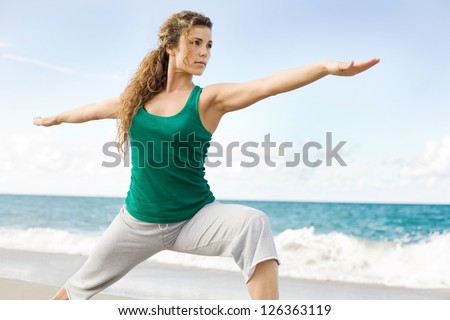 Beautiful female doing yoga warrior pose at the beach with copy space - stock photo