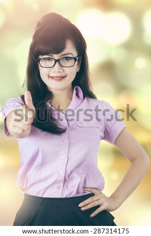 Beautiful female entrepreneur showing thumb up on the camera, shot with light glitter background - stock photo