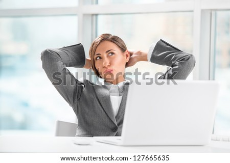 Beautiful female executive relaxing with hands behind head