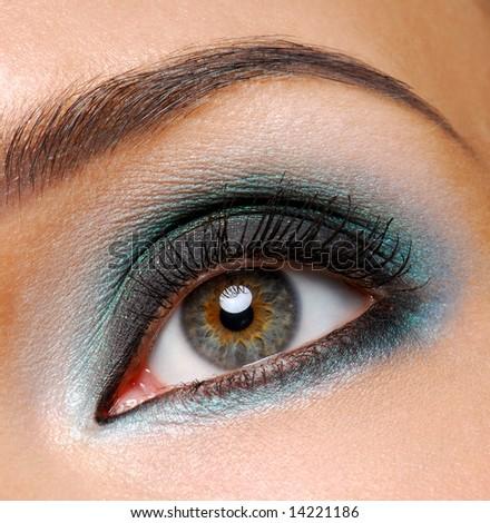 Beautiful female eye with fashion ceremonial makeup - stock photo